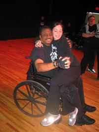 A young woman sits on the lap of a man in a wheelchair.