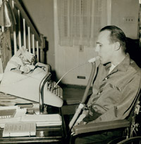 A seated man types on a typewriter using a mouth stick.