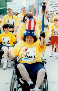 Ana Jennings, a wheelchair user, rides through the street holding a torch.