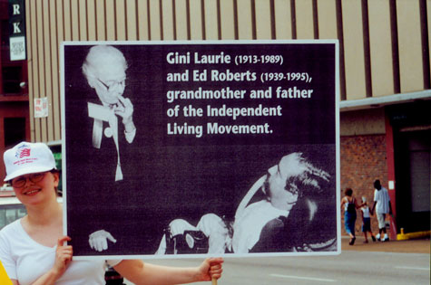 A woman holds up a sign that depicts Gini Laurie and Ed Roberts and includes the caption 'Gini Laurie and Ed Roberts, grandmother and father of the Independent Living Movement.'