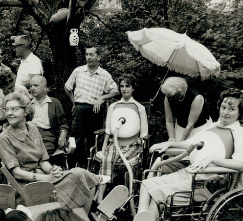 A gathering of 7 people in the backyard of Gini Laurie, several of whom are wearing turtle shells, mobile respiratory devices that attach to the upper abdomen to aid in breathing.