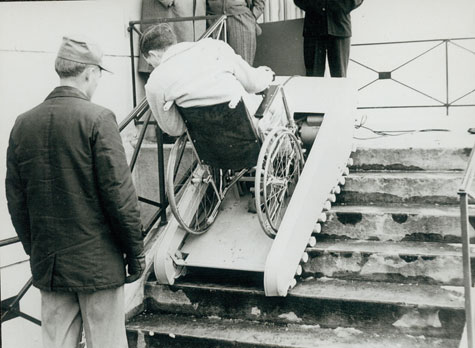 A man in a wheelchair climbs a staircase with the aid of a ramp that moves up the steps with him.