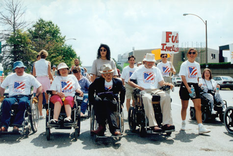 Protesters ride with Justin Dart Jr. and Max Starkloff in a St. Louis march through the streets. Many of the protesters use wheelchairs.