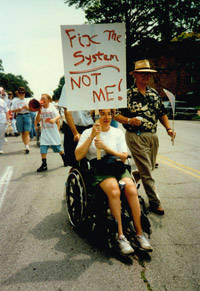 A protester who uses a wheelchair holds up a sign that says 'Fix The System: Not Me.'