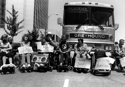 A group of people in wheelchairs gathers in front of a Greyhound bus with signs that read 'All Aboard,' 'We will ride,' and 'Lifts on Hounds.'