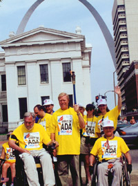 Max Starkloff, Representative Richard Gephardt, Colleen Kelly Starkloff, and Jim Tuscher stand together downtown in the shadow of the St. Louis Arch. Gephardt holds aloft the torch from Spirit of the ADA Torch Relay.